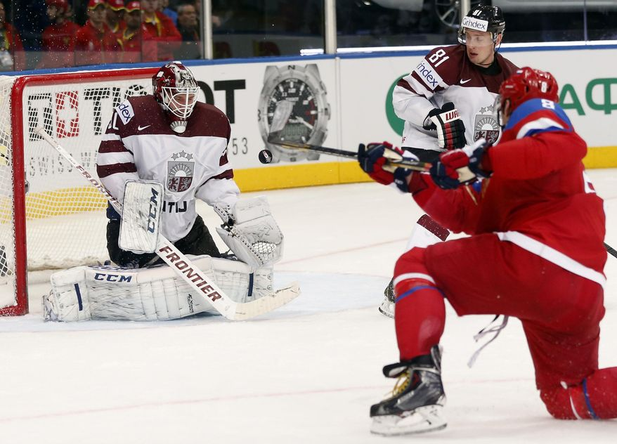 Russia forward Alexander Ovechkin, right, attempts to score past Latvia goaltender Kristers Gudlevskis during the Group B preliminary round match between Russia and Latvia at the Ice Hockey World Championship in Minsk, Belarus, Saturday, May 17, 2014. (AP Photo/Darko Bandic)