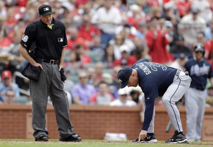 Atlanta Braves manager Fredi Gonzalez, right, points to home plate after being ejected from the game by home plate umpire Ron Kulpa, left, during the fifth inning of a baseball game against the St. Louis Cardinals on Saturday, May 17, 2014, in St. Louis. (AP Photo/Jeff Roberson)