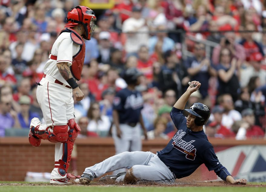 Atlanta Braves' Andrelton Simmons, right, scores on a throwing error by St. Louis Cardinals second baseman Kolten Wong as Cardinals catcher Yadier Molina, left, stands by during the second inning of a baseball game on Saturday, May 17, 2014, in St. Louis. (AP Photo/Jeff Roberson)
