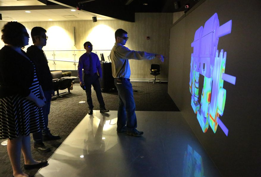 Mitchell Nollar from ArcelorMittal points out details of a vertical edger used in the processing of steel at the CIVS virtual reality lab at Purdue Calumet. Looking on are students Hannah Amor, Yuanbang Sun and Bin Wu.(AP Photo/The Times,John J. Watkins)