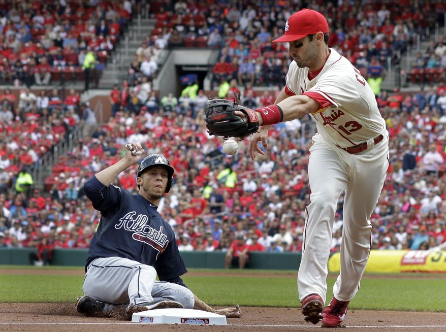 Atlanta Braves' Andrelton Simmons, left, is safe at third as the throw gets away from St. Louis Cardinals third baseman Matt Carpenter during the second inning of a baseball game Saturday, May 17, 2014, in St. Louis. Simmons was able go on to score and Cardinals second baseman Kolten Wong was charged with a throwing error on the play. (AP Photo/Jeff Roberson)
