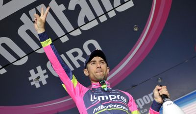 Italy's Diego Ulissi celebrates on the podium after winning the eighth stage of the Giro d'Italia, Tour of Italy cycling race, from Foligno to Montecopiolo, Italy, Saturday May 17, 2014. A final push from Diego Ulissi saw the Italian win a tough eighth stage as the Giro d'Italia took to the mountains Saturday, while Cadel Evans ended Michael Matthews' grip on the overall lead. (AP Photo/Marco Alpozzi)