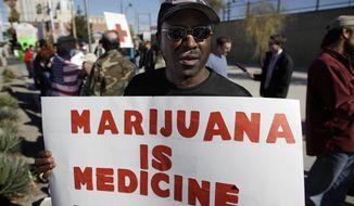 ** FILE ** This Jan. 12, 2011, file photo shows Anthony Hampton demonstrating in favor of medical marijuana in Las Vegas. (AP Photo/Julie Jacobson, file)