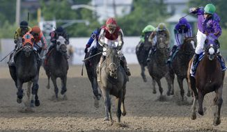 Jockey Victor Espinoza, right, celebrates aboard California Chrome after winning the 139th Preakness Stakes horse race at Pimlico Race Course, Saturday, May 17, 2014, in Baltimore. (AP Photo/Patrick Semansky)