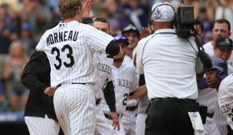Colorado Rockies' Justin Morneau, left, is mobbed by teammates at home plate after Morneu hit a two-run, walkoff home run against the San Diego Padres in the 10th inning of the Rockies' 8-6 victory in 10 innings of a baseball game in Denver on Sunday, May 18, 2014. (AP Photo/David Zalubowski)