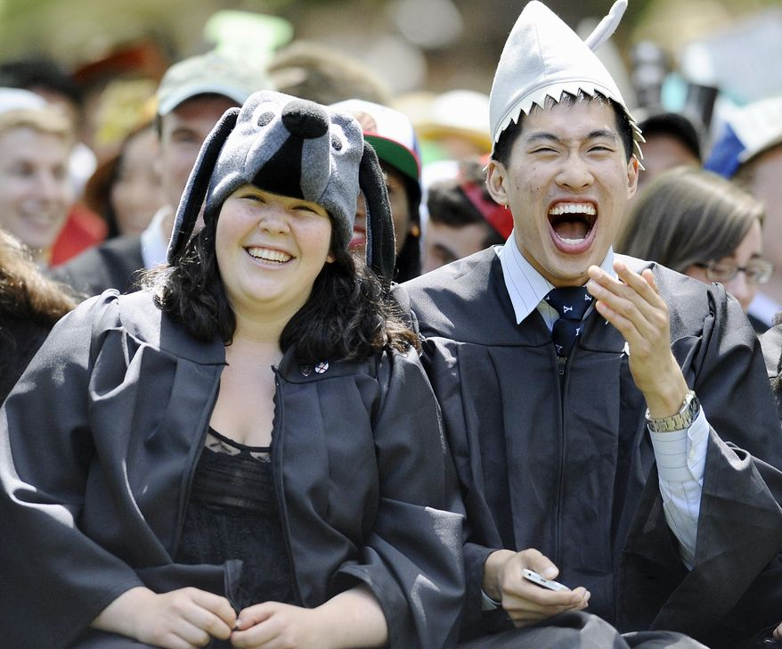 Miriam Rock of Philadelphia, left, and Jack Shu of Potomac, Md., right, react as Secretary of State John Kerry delivers the Class Day address at Yale University, Sunday, May 18, 2014, in New Haven, Conn. (AP Photo/Jessica Hill)