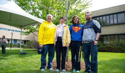 Paul DeWolf's father Thom, mother Kris, sister Rebekah and and brother Joshua stand in front of the tree in the courtyard of the University of Michigan Medical School that has been dedicated to slain University of Michigan medical student Paul DeWolf in the courtyard of the University of Michigan Medical School, Sunday, May 18, 2014. (AP Photo/The Ann Arbor News, Courtney Sacco)