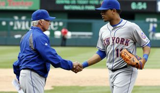New York Mets manager Terry Collins, left, shakes hands with center fielder Juan Lagares after a baseball game against the Washington Nationals at Nationals Park Saturday, May 17, 2014, in Washington. The Mets won 5-2. (AP Photo/Alex Brandon)