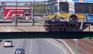 A Massachusetts Bay Transportation Authority bus hangs over the Massachusetts Turnpike after crashing on Centre Street in Newton, Mass., Sunday, May 18, 2014. Seven passengers and the bus driver were transported to a hospital with non-life-threatening injuries, MBTA spokeswoman Kelly Smith. Three other passengers declined medical treatment. (AP Photo/Boston Herald, Matt Stone)