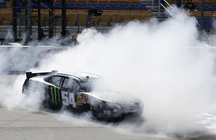 Sam Hornish Jr. does a burnout after winning the NASCAR Nationwide auto race, Sunday, May 18, 2014, at Iowa Speedway in Newton, Iowa. (AP Photo/Charlie Neibergall)