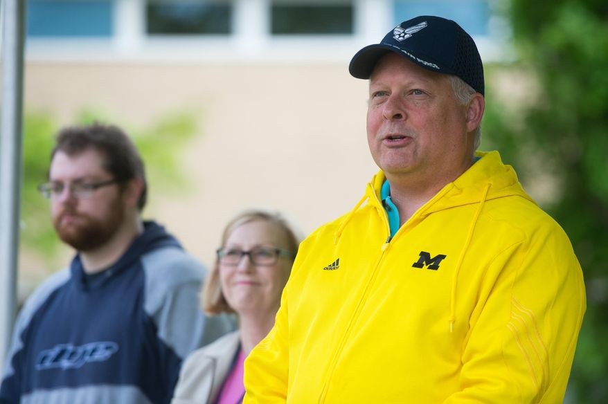 Thom DeWolf, father to Paul, welcomes the other 50 people to the tree dedication in honor of slain University of Michigan medical student  Paul DeWolf in the courtyard of the University of Michigan Medical School, Sunday, May 18, 2014.  (AP Photo/ The Ann Arbor News, Courtney Sacco)