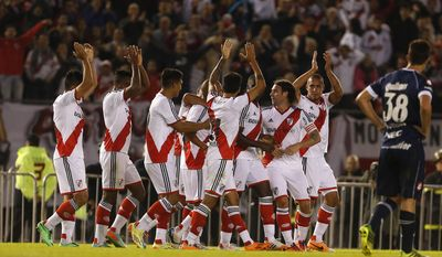 River Plate players, center, celebrate with teammate Cristian Ledesma, center, after he scored against Quilmes during an Argentine league soccer match in Buenos Aires, Argentina, Sunday, May 18, 2014. (AP Photo/Victor R. Caivano)