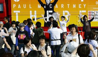 """Fans take photos of themselves in front of a tour truck bearing an image of Paul McCartney after his concert was cancelled at Natinal Stadium, the site of his concert in Tokyo, Sunday, May 18, 2014. McCartney has canceled his second concert in Japan, as well as the makeup performance for the one nixed a day earlier, and apologized to his fans for still being sick with a virus. The former Beatle said on his """"Out There Japan Tour 2014"""" site that he wanted to perform Sunday against doctors' orders, but his team wouldn't allow it. (AP Photo/Kyodo News) JAPAN OUT, CREDIT MANDATORY"""