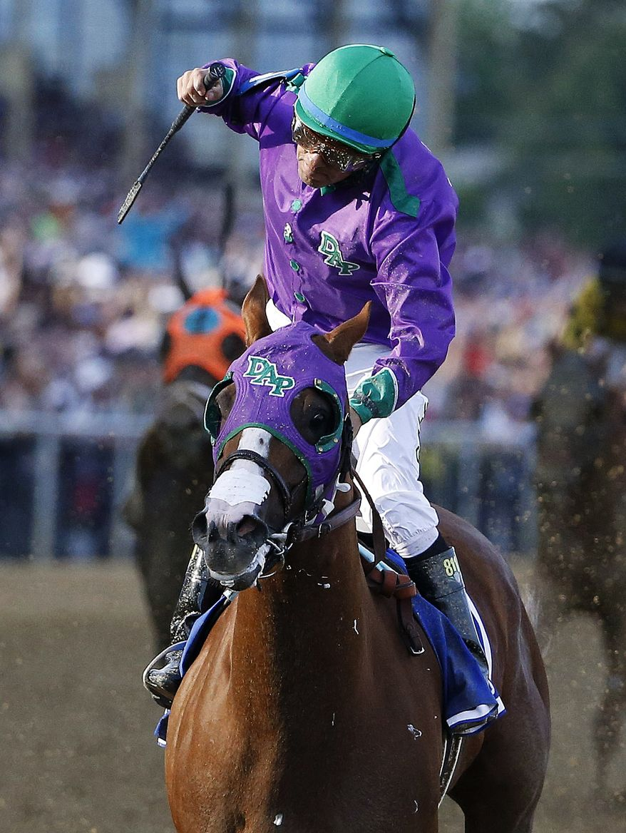 Jockey Victor Espinoza celebrates aboard California Chrome after winning the 139th Preakness Stakes horse race at Pimlico Race Course, Saturday, May 17, 2014, in Baltimore. (AP Photo/Matt Slocum)