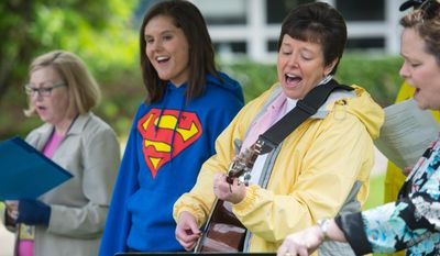"""Kris DeWolf leads the crowed in the song """" My Savior, My God"""" during a tree dedication in honor of slain University of Michigan medical student Paul DeWolf in the courtyard of the University of Michigan Medical School, Sunday, May 18, 2014. (AP Photo/The Ann Arbor News, Courtney Sacco)"""