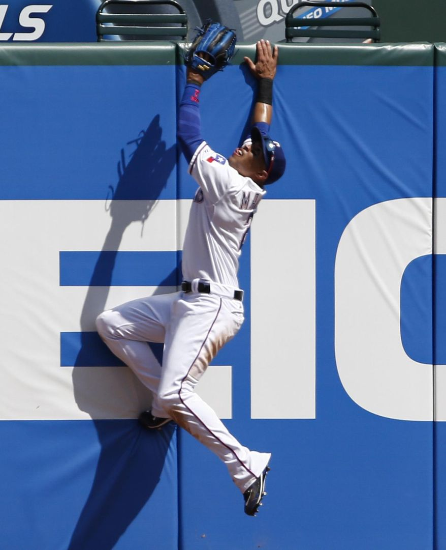 Texas Rangers center fielder Leonys Martin leaps unsuccessfully for the ball hit for a home run by Toronto Blue Jays' Edwin Encarnacion during the sixth inning of a baseball game, Sunday, May 18, 2014, in Arlington, Texas. The Rangers won 6-2. (AP Photo/Jim Cowsert)