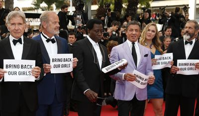 """The cast of The Expendables 3, from left, Kelsey Grammer, Wesley Snipes, Sylvester Stallone, Ronda Rousey and Mel Gibson hold up banners reading, """"Bring back our girls"""", part of a campaign calling for the release of nearly 300 abducted Nigerian schoolgirls being held by Nigerian Islamic extremist group Boko Haram, as they arrive for the screening of The Homesman at the 67th international film festival, Cannes, southern France, Sunday, May 18, 2014. (AP Photo/Alastair Grant)"""