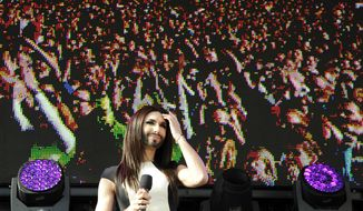 Austrian singer and Eurovision Song Contest winner Conchita Wurst performs on stage   in front of the federal chancellery in Vienna, Austria on Sunday, May 18, 2014.  Bearded drag queen Conchita Wurst had made a triumphant return to Austria last week  after winning the Eurovision Song Contest in Copenhagen in what the country's president called a victory for tolerance in Europe. Video screen in background shows waving fans.  (AP Photo/Hans Punz)