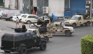 In this file image made from video provided by the Libyan national army via AP Television, Tripoli joint security forces on vehicles with heavy artillery stand guard on the entrance road to the parliament area after troops of Gen. Khalifa Hifter targeted Islamist lawmakers and officials at the parliament in Tripoli, Libya, on Sunday, May 18, 2014. (AP Photo/Libyan national army) ** FILE **