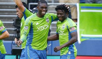 SoundersFC's Jalil Anibaba, left, congratulates teammate Obafemi Martins after Martins scored a goal against the San Jose Earthquakes in the first half in an MLS matchup on Saturday, May 17, 2014, at CenturyLink Field in Seattle, Wash. Seattle won, 1-0. (AP Photo/The Seattle Times, John Lok)