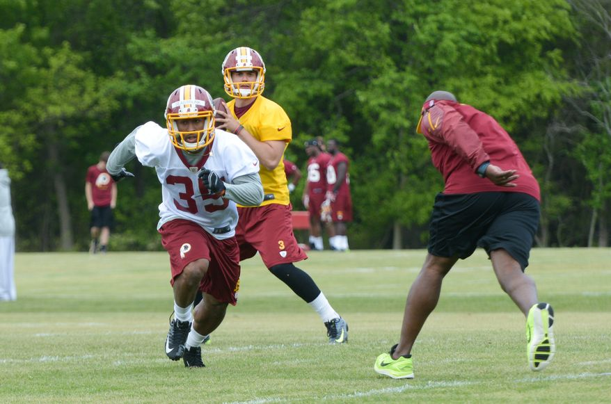 Running back Lache Seastrunk, runs a route as free agent quarterback Tommy Rees prepares to throw him a pass during the Washington Redskins rookie minicamp on Saturday, May 17 at Redskins Park in Ashburn.  Rees was released from the team late Saturday. Khalid Naji-Allah/ Special to The Washington Times