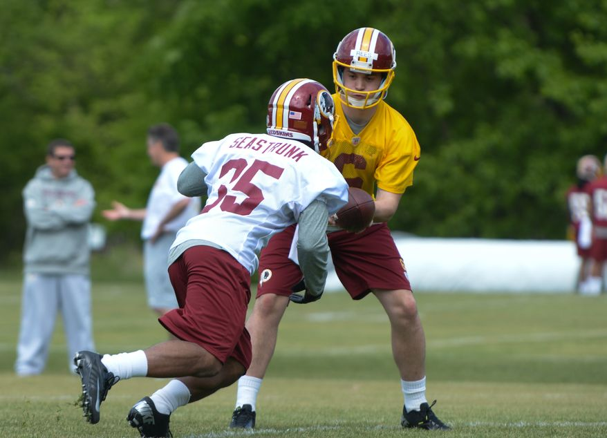Undrafted free agent quarterback Tommy Rees hands off to sixth-round draft pick running back Lache Seastrunk during the Washington Redskins rookie minicamp on Saturday, May 17 at Redskins Park in Ashburn.  Rees was released from the team late Saturday. Khalid Naji-Allah/ Special to The Washington Times