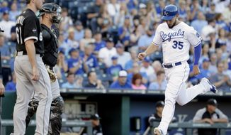 Kansas City Royals' Eric Hosmer (35) runs past Chicago White Sox starting pitcher Scott Carroll (61) and catcher Tyler Flowers to score on single by Billy Butler during the first inning of a baseball game Monday, May 19, 2014, in Kansas City, Mo. (AP Photo/Charlie Riedel)