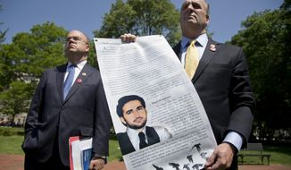 Rep. Dan Kildee, D-Mich., right, accompanied by Rep. James McGovern, D-Mass., holds a poster with the image and story of one of his constituents, Amir Hekmati, a former Marine incarcerated in Iran since 2011, during a gathering in Lafayette Park across the street from the White House in Washington, Monday, May 19, 2014, with family members and supporters calling for Hekmati's release.  (AP Photo/Carolyn Kaster)