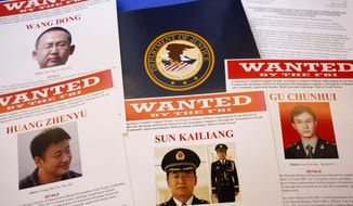 Press materials are displayed on a table of the Justice Department in Washington, Monday, May 19, 2014, before Attorney General Eric Holder was to speak at a news conference. Holder was announcing that a U.S. grand jury has charged five Chinese hackers with economic espionage and trade secret theft, the first-of-its-kind criminal charges against Chinese military officials in an international cyber-espionage case. (AP Photo/Charles Dharapak)