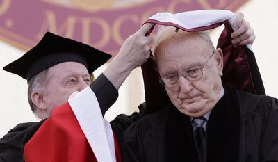 Former Boston Celtic player and NBA hall of fame member Bob Cousy, right,  his hooded by Boston College President William Leahy during the Boston College commencement ceremony, Monday, May 19, 2014, in Boston. Cousy, along with Secretary of State John Kerry and three others  received honorary Ph. D. degrees during the college's 2014 commencement. (AP Photo/Stephan Savoia)