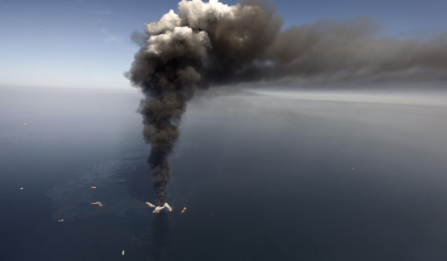 In this Wednesday, April 21, 2010, file photo, oil can be seen in the Gulf of Mexico, more than 50 miles southeast of Venice on Louisiana's tip, as a large plume of smoke rises from fires on BP's Deepwater Horizon offshore oil rig. (AP Photo/Gerald Herbert, File)