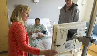 In this photo taken May 16, 2014, Providence Sacred Heart Medical Center social worker Marilyn Stolp, left, connects new mom Carolina Salazar-Aleman and her husband Ramon Sandoval with a remote Spanish interpreter at Sacred Heart Medical Center in Spokane, Wash. Providence Health now uses video remote interpreters in 30 of its regional hospitals and clinics. The system provides live interpreting to help staff work with patients who are either deaf or don't speak English. (AP Photo/The Spokesman-Review, Colin Mulvany) COEUR D'ALENE PRESS OUT.