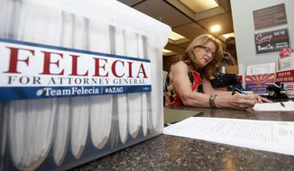 Democrat Felecia Rotellini signs documents at the Arizona capitol  on Monday, May 19, 2014, in Phoenix in order to file her nominating petitions to officially qualify for the ballot to run for Arizona attorney general.  Rotellini says she is ready to take on either Attorney General Tom Horne or his Republican primary opponent in the November general election. (AP Photo/Ross D. Franklin)