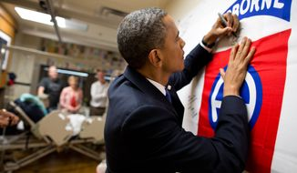 President Barack Obama autographs a banner while visiting a wounded service member at Walter Reed National Military Medical Center in Bethesda, Md., June 28, 2012. (Official White House Photo by Pete Souza)