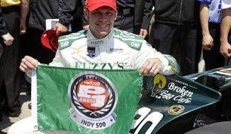 Ed Carpenter displays the P1 award flag after winning the pole during qualifications for the Indianapolis 500 IndyCar auto race at the Indianapolis Motor Speedway in Indianapolis, Sunday, May 18, 2014. (AP Photo/Michael Conroy)