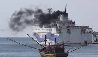 A ship carrying Chinese workers leaves Vung Ang port, Ha Tinh province, Vietnam Monday, May 19, 2014.  Watched over by riot police, hundreds of Chinese workers left Vietnam on Monday on ships chartered by their government after deadly unrest broke out last week amid a dispute over sovereignty claims in the South China Sea. (AP Photo/Hau Dinh)