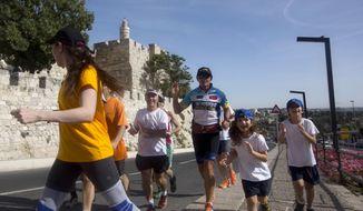 "Australian runner Pat Farmer, center, runs near the Tower of David in Jerusalem's old city, Monday, May 19, 2014. The Australian marathon runner has completed his 1,500 kilometer-long ""Middle East Peace Run,"" cutting the finish line in Jerusalem. (AP Photo/Sebastian Scheiner)"