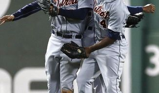 Detroit Tigers' J.D. Martinez, left, Torii Hunter, right, and Austin Jackson, behind, celebrate after defeating the Boston Red Sox 6-2 in a baseball game in Boston, Sunday, May 18, 2014. (AP Photo/Michael Dwyer)