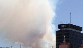 Smoke billows across the downtown Reno skyline on Sunday, May 18, 2014, from a wildfire burning in the wilderness in the Sierra foothills above the city's southwest side. About 150 firefighters with the help of three helicopters were fighting the blaze on Monday. Officials said there was no immediate threat to homes. (AP Photo/Scott Sonner)