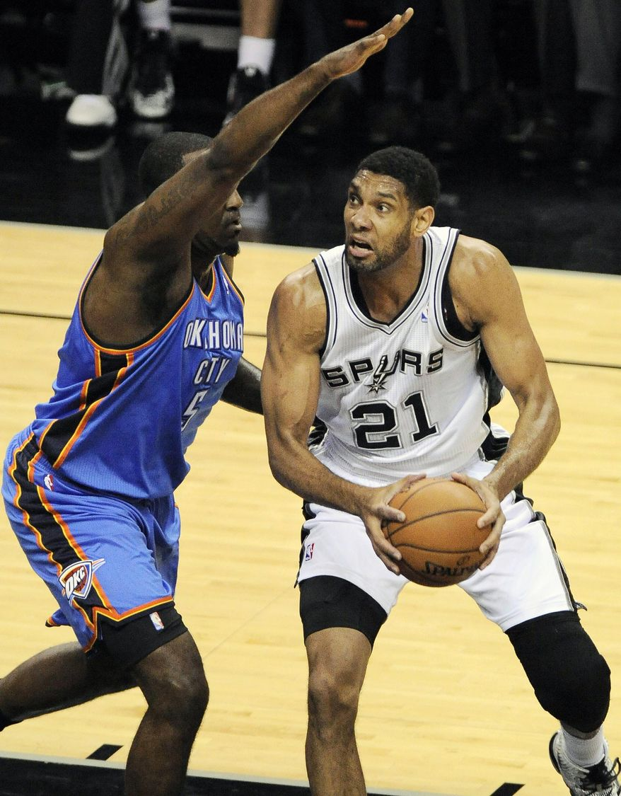San Antonio Spurs forward Tim Duncan, right, shoots against Oklahoma City Thunder center Kendrick Perkins during the first half of an NBA playoff basketball game on Monday, May 19, 2014, in San Antonio. (AP Photo/Darren Abate)