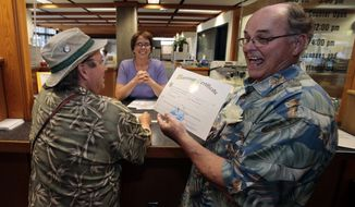 Bruce Carlson, right, holds his ceremonial marriage license to marry his partner, Matt Friday, at the Lane County courthouse Monday, May 19, 2014. Carlson, 72, and Friday, 63, were first in line at the county Deeds and Records office to apply for a license. (AP Photo/The Register-Guard, Paul Carter)