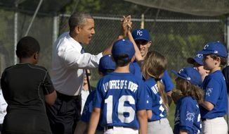 President Barack Obama greets players during an unannounced stop to surprise members of the Northwest little league baseball teams at Friendship park in Washington, Monday, May 19, 2014. Obama stopped to meet with the players before heading off to a private Democratic fundraiser. (AP Photo/Pablo Martinez Monsivais)