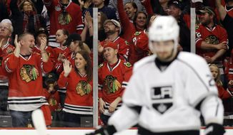 Chicago Blackhawks fans celebrates after Duncan Keith scored as Los Angeles Kings' Slava Voynov (26) looks down during the second period in Game 1 of the Western Conference finals in the NHL hockey Stanley Cup playoffs in Chicago on Sunday, May 18, 2014. (AP Photo/Nam Y. Huh)