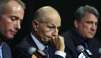 Boston Bruins owner Jeremy Jacobs, center, listens to a reporter's question during a news conference in Boston, Tuesday, May 20, 2014. The Bruins were eliminated from the NHL hockey playoffs by the Montreal Canadiens.  At left is Jeremy's son Charlie Jacobs, principal of Delaware North Companies, Inc. and the Boston Bruins and at right is Cam Neely, Bruins president. (AP Photo/Charles Krupa)
