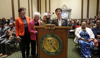 New Washington state Supreme Court Justice Mary Yu recites an oath during her swearing-in to the bench Tuesday, May 20, 2014, in Olympia, Wash. She stands with supporters Anne Levinson, left, Ruth Woo and Phyllis Gutierrez Kenney. Yu, a former King County Superior Court judge, was sworn in as the newest member of the court, marking the first time the high court has had an openly gay justice. Yu, whose mother is from Mexico and father is from China, is also the first Asian American and first female Hispanic member of the court. (AP Photo/Elaine Thompson)