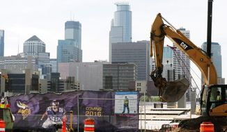 The Minneapolis skyline rises in the background as work continues on the new Minnesota Vikings NFL football stadium,Tuesday, March 20, 2014, in Minneapolis. Minneapolis will host the 2018 Super Bowl after a vote by owners Tuesday rewarded the city for its new stadium deal  (AP Photo/Jim Mone)