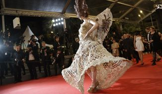 An unidentified guest walks on the red carpet as she arrives for the screening of Coming Home (Gu Lai) at the 67th international film festival, Cannes, southern France, Tuesday, May 20, 2014. (AP Photo/Thibault Camus)