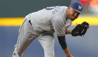 Milwaukee Brewers starting pitcher Yovani Gallardo delivers in the first inning of a baseball game against the Atlanta Braves on Tuesday, May 20, 2014, in Atlanta. (AP Photo/Todd Kirkland)