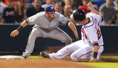 Milwaukee Brewers shortstop Jeff Bianchi (14) tags out Atlanta Braves' Chris Johnson (23) as he slides into third in the fifth inning of a baseball game Tuesday, May 20, 2014, in Atlanta. (AP Photo/Todd Kirkland)
