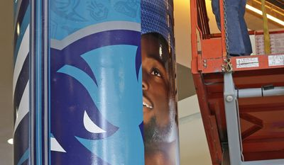 A worker covers a former Charlotte Bobcats sign with a Charlotte Hornets sign at Time Warner Cable Arena before a news conference to announce officially changing the NBA basketball team's name from Bobcats to Hornets in Charlotte, N.C., Tuesday, May 20, 2014. (AP Photo/Chuck Burton)
